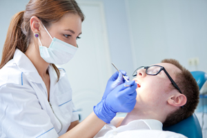 Hygienist cleaning patients teeth